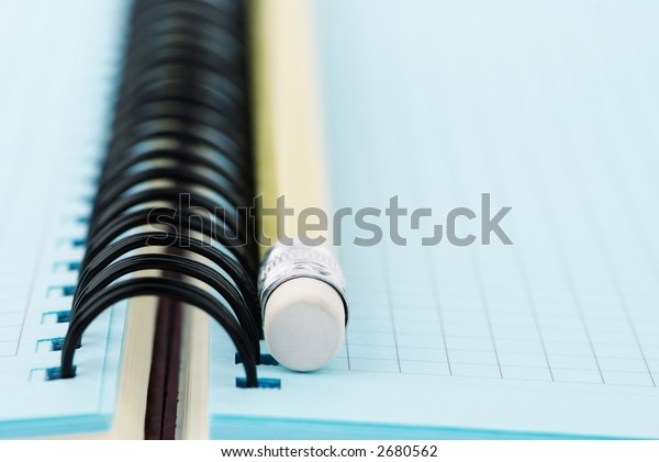 pen and blue notebook (empty space for your text,special photo f/x,focus point on metal part of the pencil)