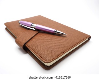 Pen and book leatherette on white background