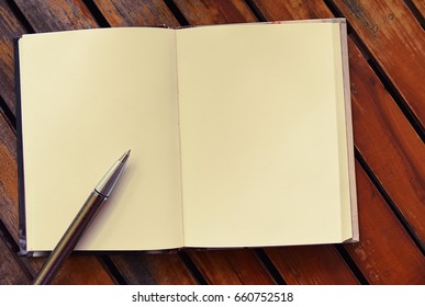 Pen and book open blank pages on old brown wood paneling,Space on the page for images or text