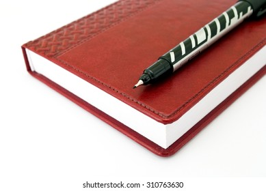 Pen and brown diary on the white background