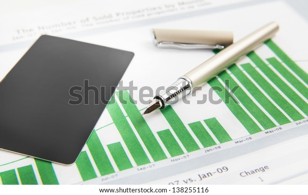 a pen and business card on the business papers