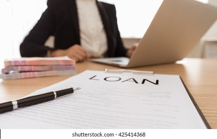 Pen and business loan application form ,money with bank employees approve contract in background.