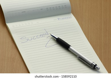 Pen and business plan notebook on wooden desk,succeed in bussiness concept