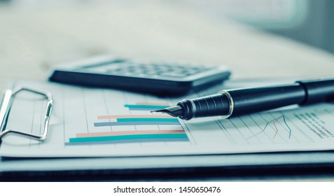Pen, calculator and financial graph on a workplace of the busine