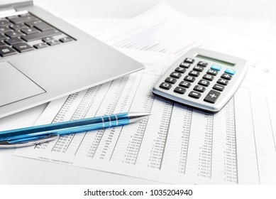 pen, calculator and laptop lying on a financial report with number charts on the desk in the office, concept for business, finance and taxes, copy space, selected focus