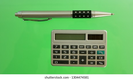 A pen and calculator on the color background