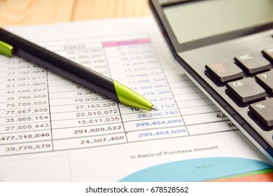 Pen and calculator on finance/business report on wood table concept of finance background, financial analysis.