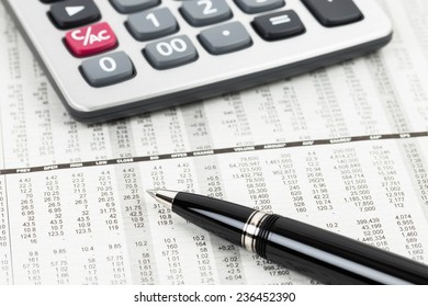 Pen and calculator on stock price detail financial newspaper
