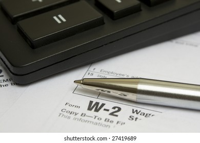 Pen and calculator on W-2 tax form