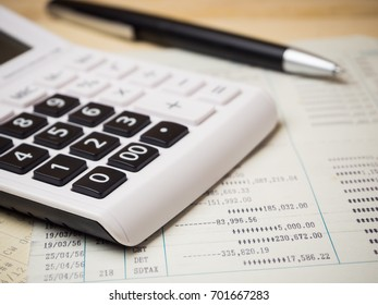 A pen with calculator over account book on wooden background for finance and banking concept.