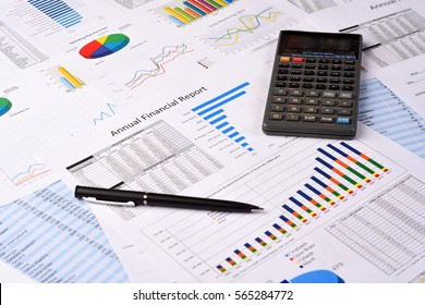 Pen and Calculator over Business Financial Reports