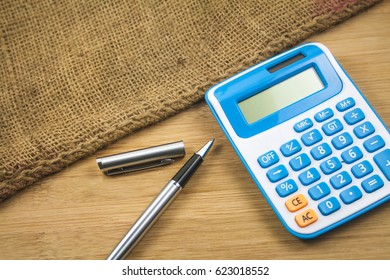 Pen and calculator over the sackcloth.