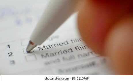 Pen and checkbox in blank tax form. Focus on married filing jointly status