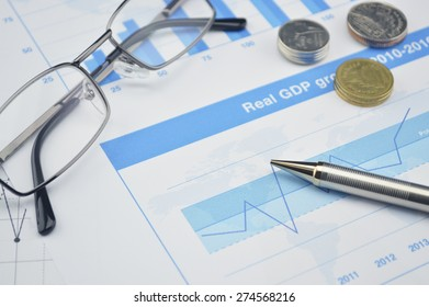 Pen, coin and glasses on financial chart and graph, accounting background