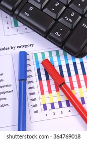 Pen and computer keyboard on financial chart, business concept, analysis of sales plan, business report, business work station with paperwork