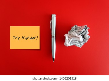 A pen and a crumpled paper on red background with a yellow note written TRY HARDER. Concept of first time writting / writers block/ journey to be a good writer.