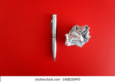 A pen and a crumpled paper on red background with copy space on the left. Concept of first time writting / writers block/ journey to be a good writer.
