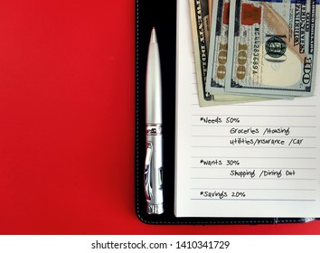 Pen and dollars banknote money on notebook with written 50/30/20 budgeting plan, on red background with copy space. Concept of setting balance on wants,needs,saving on 50/30/20 spending budget rules