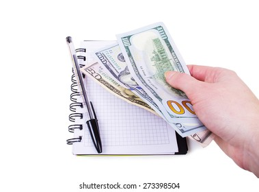 pen and dollars are on the notebook