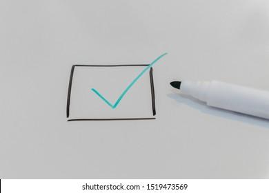 pen drawing tick symbol on blackboard