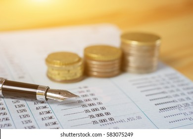Pen with Finances statement ,hand pointing business charts,coins on paper work in the office,discussing stock marketing document,book bank,vintage color