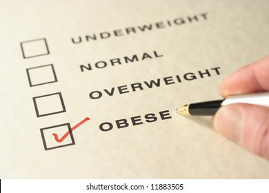 Pen and fingers pointing at an obesity check mark/box.