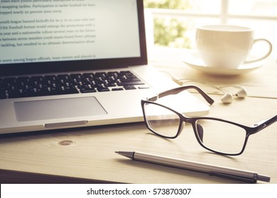 Pen and glasses with computer laptop on wood table.Inspiration moment,workspace or coffee break in the morning/ selective focus