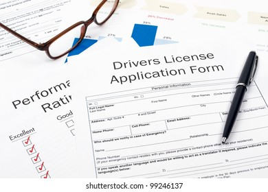 Pen, Glasses and Drivers License Application Form on desktop in business office.