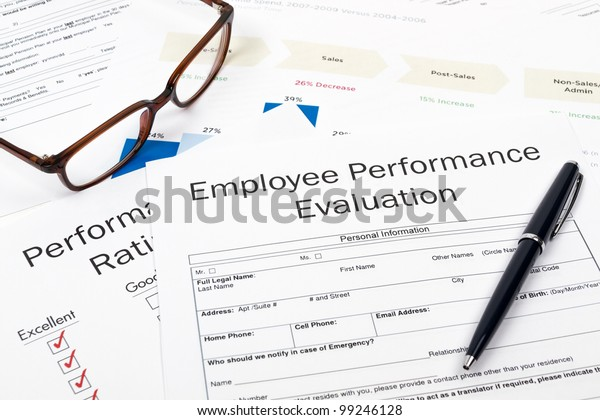 Pen, Glasses and Employee Performance Evaluation on desktop in business office.