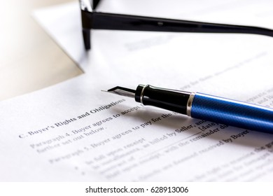 Pen and glasses lying on signed documents on office desk