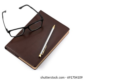 Pen glasses and notebook on a white background