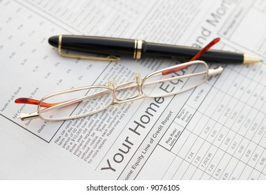 Pen and glasses on finance background