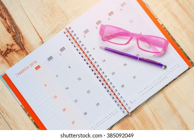 Pen with glasses on notebook calendar format