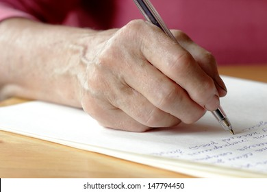 ������ pen in the hands of an elderly woman and Paper