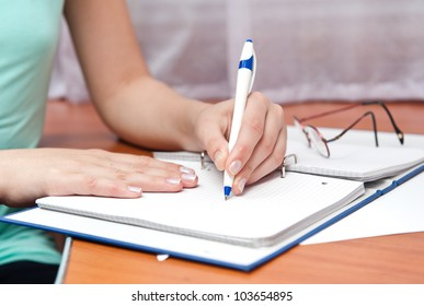 pen in left hand writing on the notebook