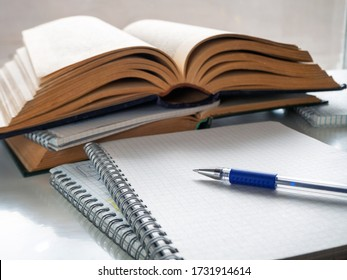 The pen lies on a blank sheet of notebook. Nearby open books and notebooks. Study, scientific work, abstract, study of literature. Background with books, notebooks and pen.