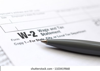 The pen lies on the tax form W-2 Wage and Tax Statement. The time to pay taxes