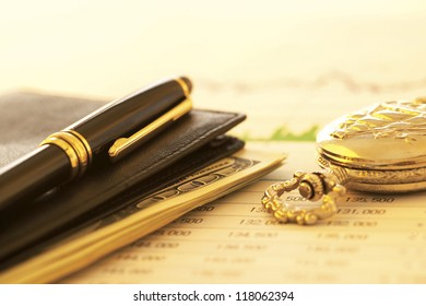 pen lying on top of wallet with stacked bills inside next to a pocket watch