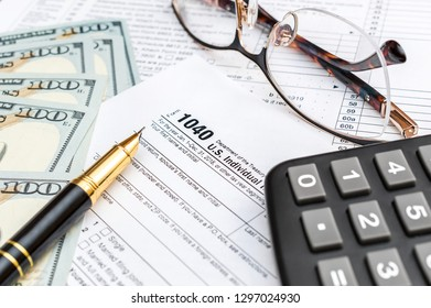 Pen, money, calculator and glasses on tax form.