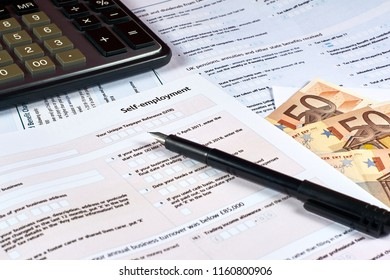 pen, money, calculator and self employment tax form