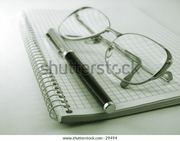 pen notebokk and glasses
