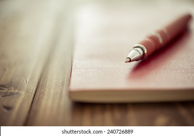 Pen and notebook up close on a rustic wooden desk