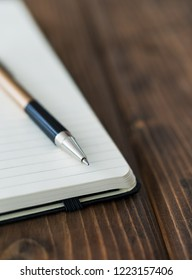 Pen and notebook up close on a wooden desk