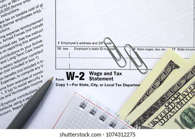 The pen, notebook and dollar bills is lies on the tax form W-2 Wage and Tax Statement. The time to pay taxes