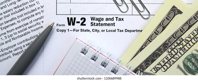 The pen, notebook and dollar bills is lies on the tax form W-2 W