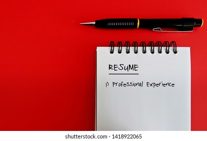 Pen and a notebook with  head title RESUME - all on red background with copy space. Concept of resume writing service.