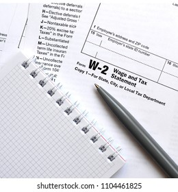 The pen and notebook on the tax form W-2 Wage and Tax Statement.