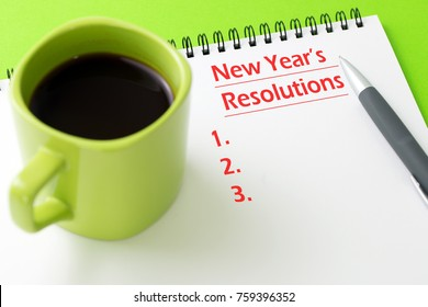 Pen and notepad with a cup of coffee to write down new years' resolutions.