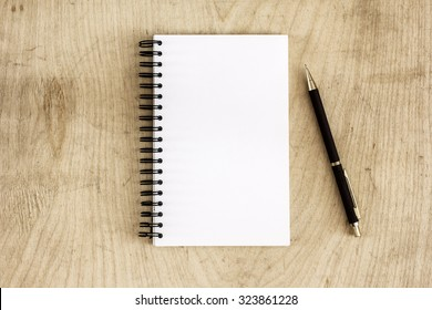 Pen and Notepad on the wooden desk