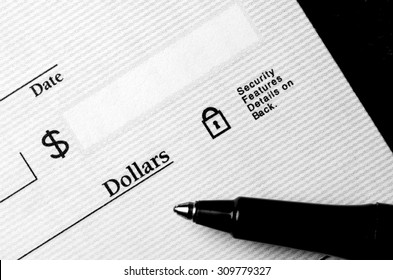 Pen on blank check to be written with dollars